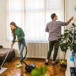 Smiling couple dusting and vacuuming their home, which can help boost indoor air quality during winter if done regularly.